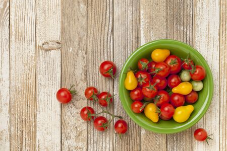 grape and cherry tomatoes in a ceramic bowl on a grunge white painted wood table Stock Photo - 10684351