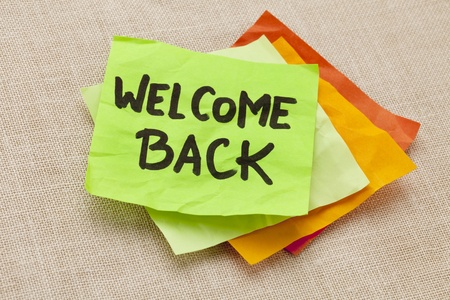 bienvenidos: bienvenida de nuevo - escritura a mano en una nota verde pegajosa contra tablero de la lona Foto de archivo