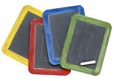 four blank vintage slate blackboards in colorful wood frames with chalk, isolated on white photo