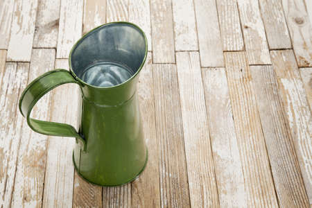 vintage metal water pitcher against grunge white painted wood table Stock Photo - 10819262