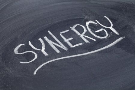 sinergia: sinergia palabra en la escritura de tiza blanca sobre pizarra