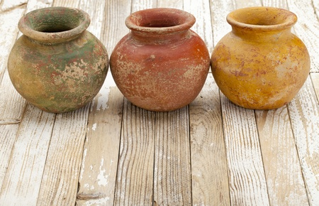 painted wood: three small  clay plant pots (mass produced planter) with rough, grunge finish,  on white rustic wood background