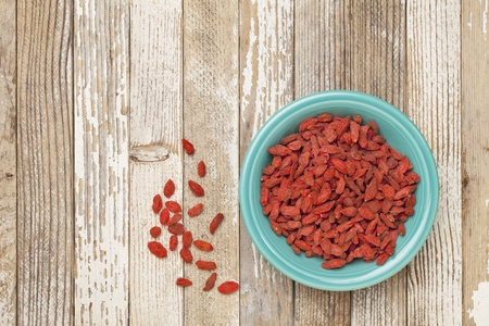 berry: dried Tibetan goji berries (wolfberries) in a blue ceramic bowl on a grunge white painted wood surface Stock Photo