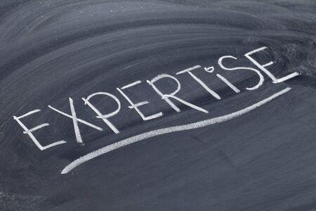 expertise: expertise word in white chalk handwriting on blackboard