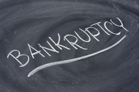 bankruptcy word in white chalk handwriting on blackboard Banco de Imagens