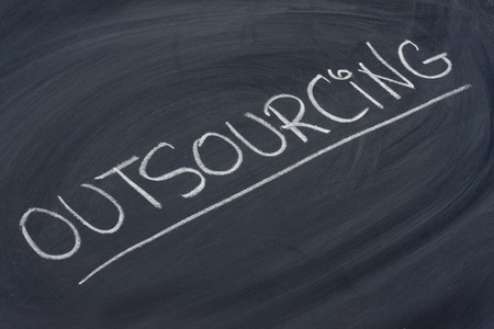 outsourcing word in white chalk handwriting on blackboard