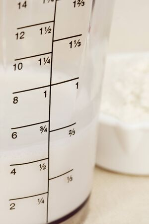 almond milk in blender beaker with ounces and cup scale and a scoop of white powder Stock Photo