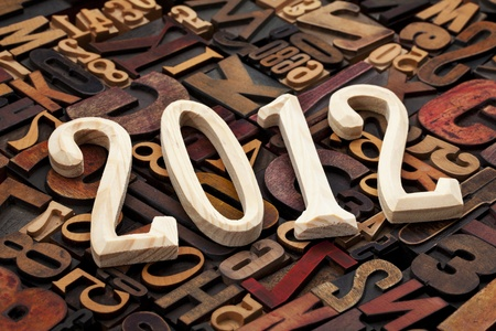 year of 2012  - wooden unfinished numbers against background of random letterpress printing blocks Stock Photo
