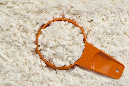 with orange and white body: antecedentes y la cuchara medidora de prote�nas de suero de leche en polvo blanco aislado Foto de archivo