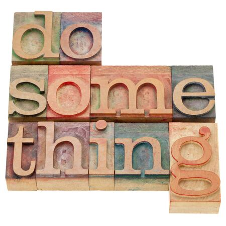 do something - a motivational phrase - isolated words in vintage wood letterpress printing blocks Stock Photo - 11179794