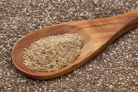 a wooden spoon of  organic ground chia seeds against the whole seeds background photo