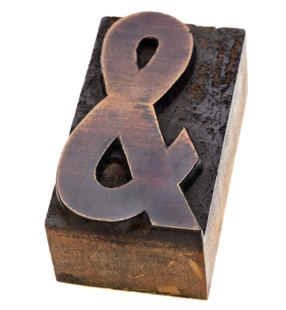 ampersand symbol  - a vintage wood letterpress type block, stained by black ink, isolated on white