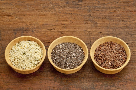 chia, flax and hemp healthy seeds in small wooden bowls Stock Photo - 11279654
