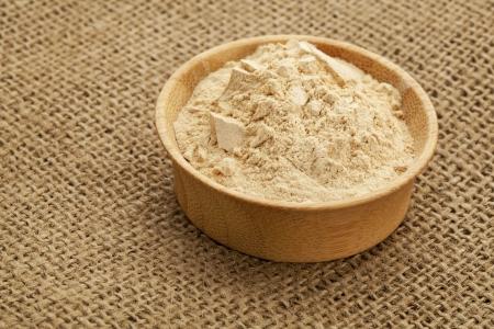 maca: maca en polvo de ra�z (suplemento de la nutrici�n - s�per de Andies) en un taz�n de madera Foto de archivo