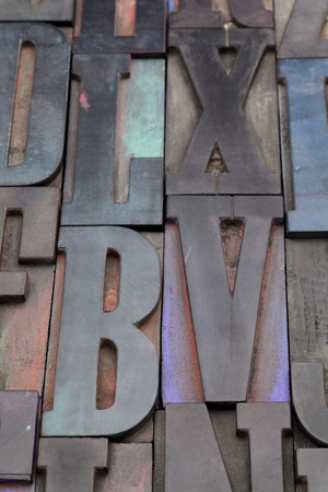 antique wood letterpress printing blocks with color ink patina, random collection with L, X, V, and B letters photo