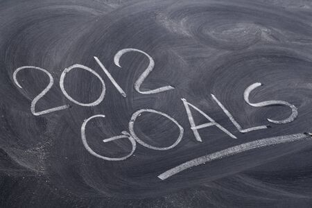 2012 goals  - white chalk handwriting on blackboard with eraser patterns Banco de Imagens