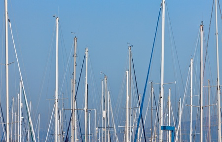 sailboat masts in a marina against blue sky and distant hills photo