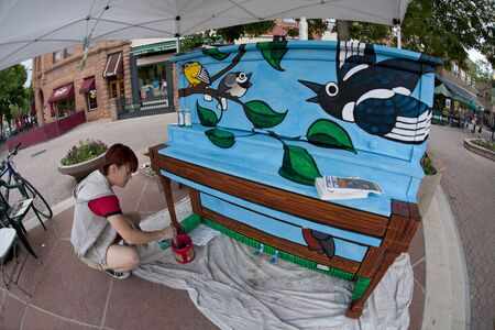fort collins: FORT COLLINS, COLORADO, USA - JUNE 19, 2011: Artist Ren Burke is painting Birdsongs mural on the piano in Fort Collins Old Town Square as part of Pianos About Town public art program. Fisheye lens perpsective. June 19, 2011. Editorial