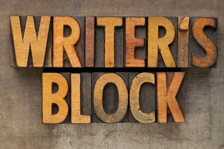person writing: writer block - text in vintage wood letterpress printing blocks stained by color inks on a grunge metal tray Stock Photo