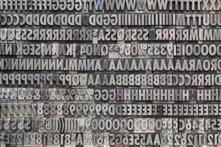 background of letters, numbers and punctuation symbols in old grunge metal movable typeset photo