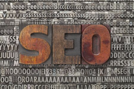 seo: seo - search engine optimization - text in vintage wood letterpress printing blocks against grunge metal typeset Stock Photo