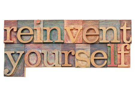 self development: reinvent yourself - personal development concept - isolated text in vintage wood letterpress printing blocks stained by color inks