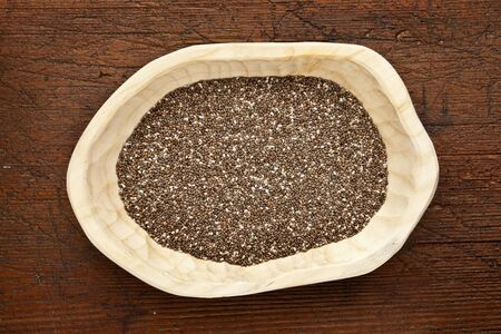 chia seed: chia seeds (Salvia Hispanica) in a rustic wood bowl against grunge dark wooden table surface, top view