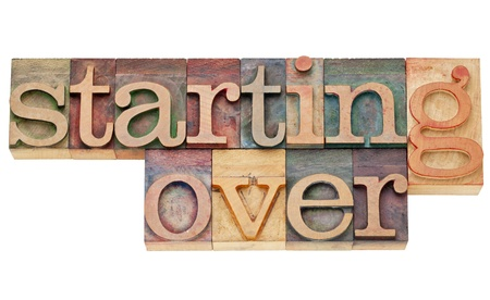 restart: starting over - isolated text in vintage wood letterpress printing blocks stained by color inks