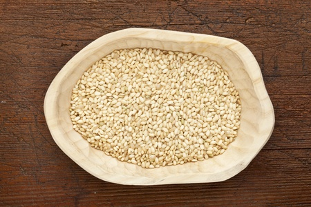 sweet brown rice grain in a rustic wood bowl against grunge dark wooden table surface, top view Stock Photo - 11788278