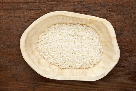 arborio rice grain, used for traditional Italian meal, risotto,  in a rustic wood bowl against grunge dark wooden table surface, top view Stock Photo - 11788251
