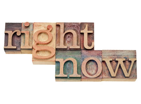 right now - action concept - isolated text in vintage wood letterpress printing blocks, stained by color inks Stock Photo - 11928820