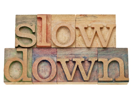 slow down -lifestyle concept - isolated text in vintage wood letterpress printing blocks, stained by color inks Stock Photo - 11928819