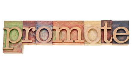 promover: promote - isolated word in vintage wood letterpress printing blocks stained by colorful inks