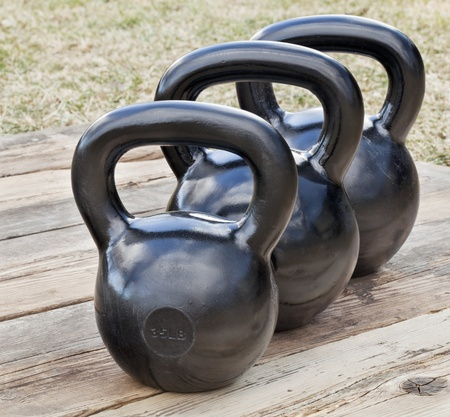 lb: three black iron kettlebell for weight training (35 and 50 lb) on wood grunge deck, outdoors with sky reflections Stock Photo