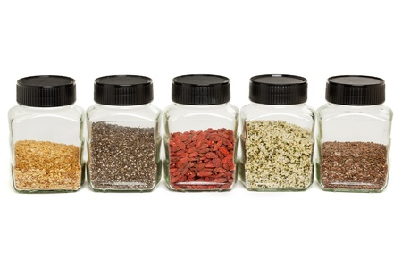 row of glass jars with healthy seeds and berries - gold and brown flax, hemp, chia seeds, goji (wolfberries) Stock Photo