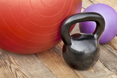 black iron kettlebell, Swiss and medicine exercise balls on wooden deck - fitness concept Stock Photo