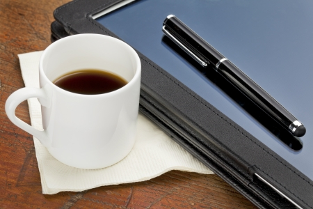 stylus pen: cup of espresso coffee, stylus pen and tablet computer in black leather case on a grunge wood