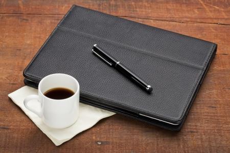 estuche: Tablet PC en el estuche de cuero con lápiz óptico y una taza de café espresso en la vieja mesa de madera vieja grunge