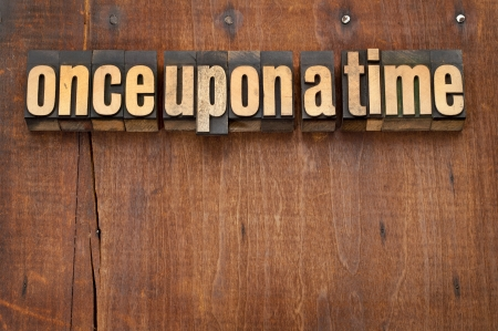 narration: once upon a time opening phrase - storytelling concept - vintage letterpress wood type text against grunge weathered wooden background