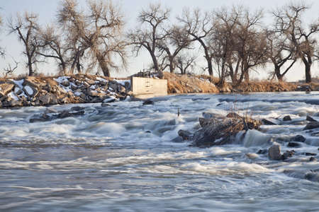 south platte river: a small dam diverting water to farmland irrigation, South Platte River in eastern Colorado near Greeley, winter scenery
