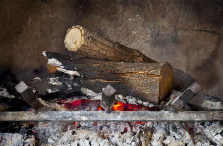 fireplace with burning wood logs on iron grate and ash Stock Photo