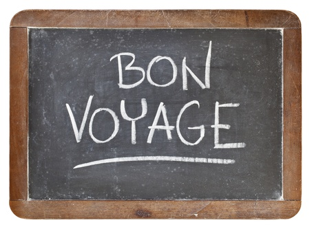 goodbye: bon voyage - travel or farewell concept - white chalk handwriting on isolated vintage slate blackboard