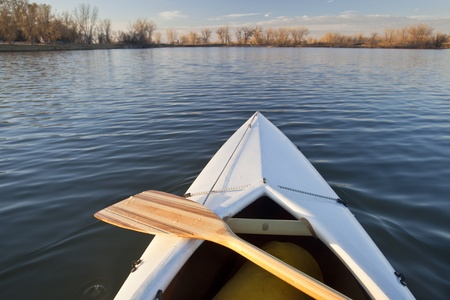 bow of white canoe with wooden paddle on a calm lake in Colorado Stock Photo - 12871493