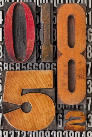 number abstract - vintage  letterpress wood type stained by color ink over metal typeset photo