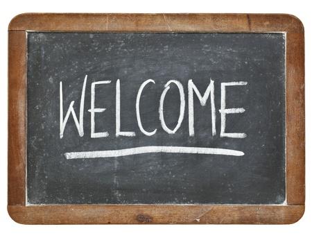 amabilidad: Bienvenido - letra de tiza blanca sobre pizarra, pizarra de la vendimia aislado Foto de archivo