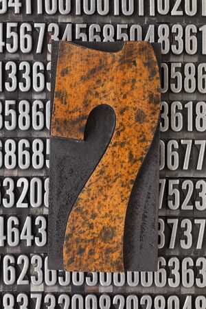 number seven in vintage letterpress wood type against background of random metal numbers Stock Photo - 12980894