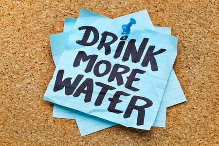 drink more water - hydration reminder - handwriting on blue sticky note posted on cork board