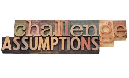 challenge assumptions - isolated text in vintage letterpress wood type Stock Photo - 13104956