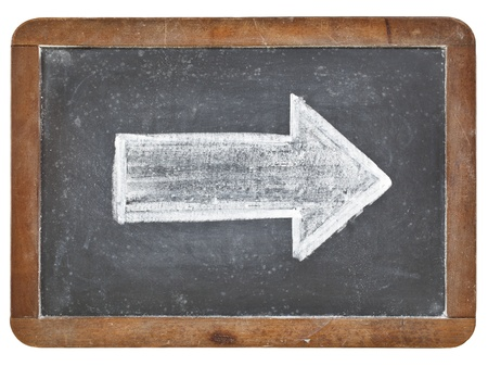 arrow - white chalk drawing on a vintage isolated slate blackboard Stock Photo - 13134746