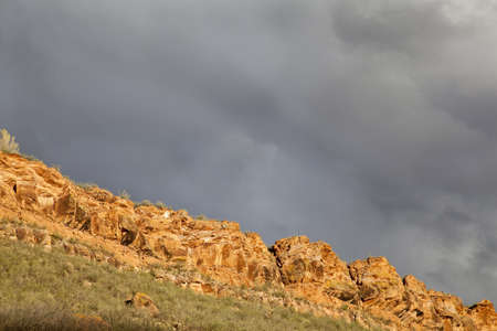 dark stormy sky over red sandstone cliff in Colorado foothills near Fort Collins, springtime with sunset light photo